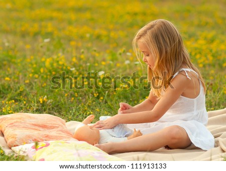Cute little girl playing with her baby toy on the meadow. - stock photo