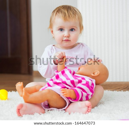 cute little girl playing with her doll at home - stock photo