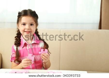 Cute little girl playing with puzzles on home interior background - stock photo