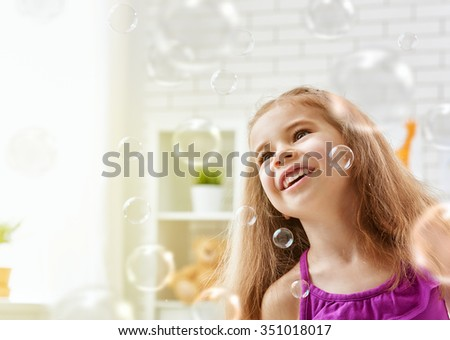 cute little girl playing with soap bubbles - stock photo