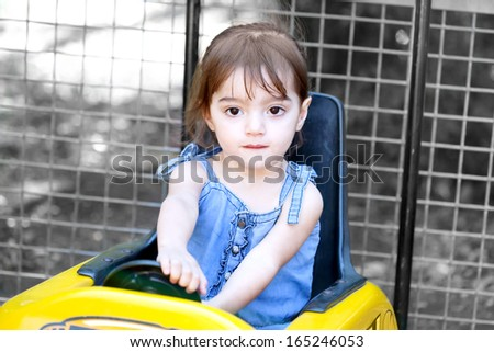 Cute little girl plays driving while sitting in a toy car - stock photo