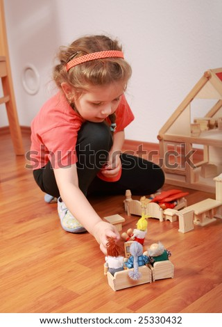 Cute little girl plays with doll's house - stock photo