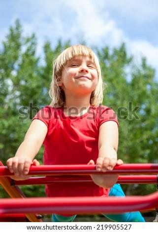 Cute little girl posing at monkey bars - stock photo