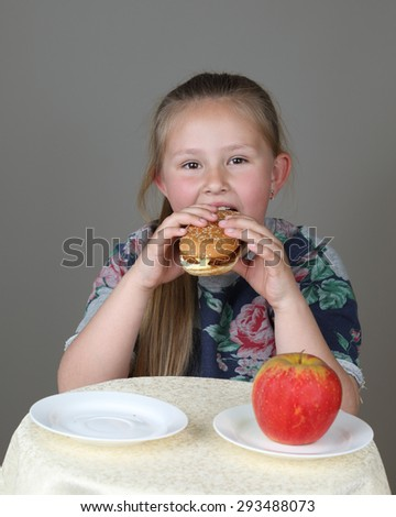 Cute little girl preferred to eat hamburger instead of apple on dark gray background - Fast food, diet and healthy eating concept - stock photo