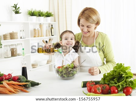Cute little girl  preparing salad with her mom - stock photo