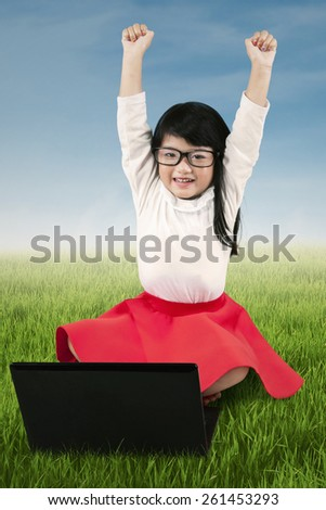 Cute little girl raise hands to celebrate her achievement while sitting on the meadow with laptop - stock photo