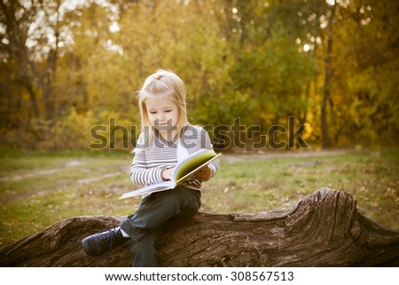 Cute little girl reading a book in autumn park - stock photo