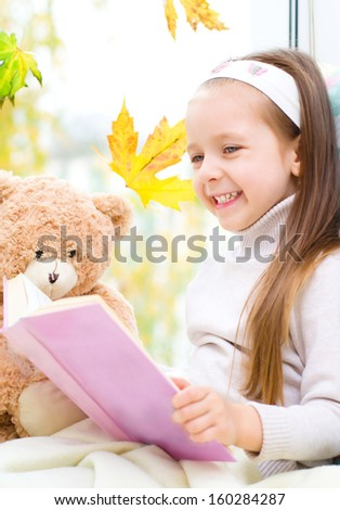 Cute little girl reading a book while sitting on the window - stock photo