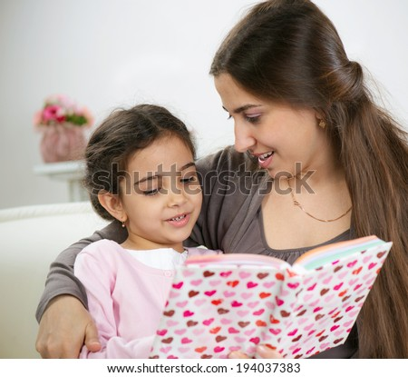 Cute little girl reading book with mother at home - stock photo