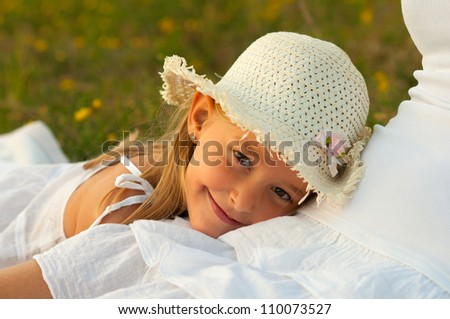 Cute little girl rests her head in her mothers lap on sunny summer day. - stock photo
