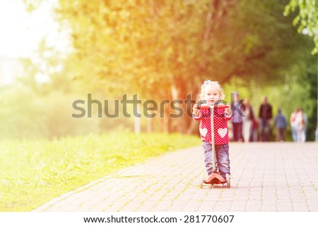 cute little girl riding scooter in summer park, early sport - stock photo