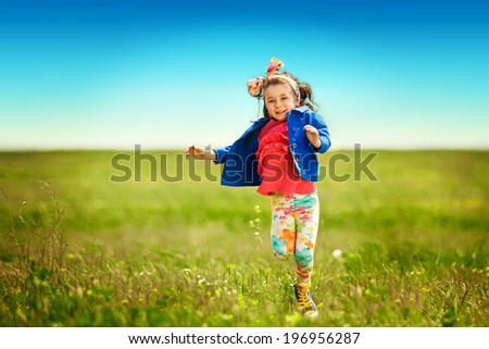 Cute little girl running on meadow in a field. Happiness, fashionable concept. - stock photo