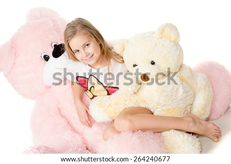 Cute little girl school age plays with a teddy bear. Isolated on white background. - stock photo