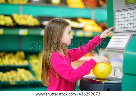Cute little girl shopping in a food store or a supermarket - stock photo