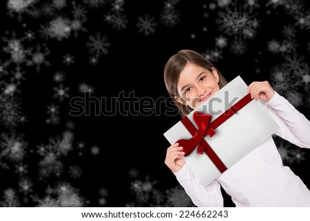 Cute little girl showing card against red christmas ribbon - stock photo