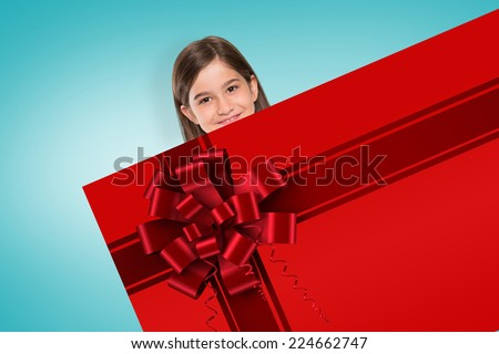 Cute little girl showing card with red christmas ribbon - stock photo