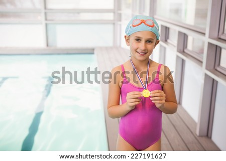 Cute little girl showing her swimming medal at the leisure center - stock photo