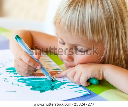 Cute little girl sitting at a table drawing - stock photo