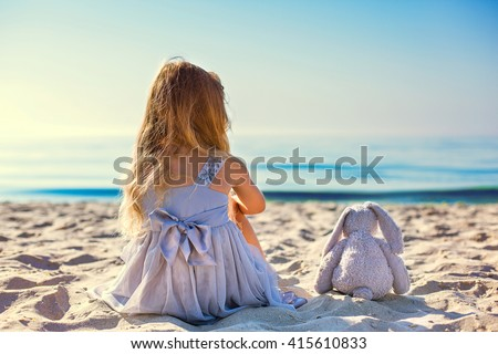 Cute little girl sitting at ocean beach - stock photo