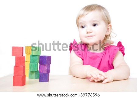 Cute little girl sitting at the table and playing with bricks - stock photo