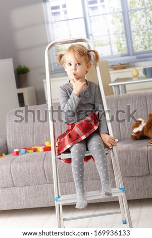 Cute little girl sitting impishly on ladder, putting forefinger on lips as calling for silence. - stock photo