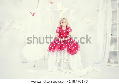 Cute little girl sitting in a white room surrounded with paper birds.  - stock photo