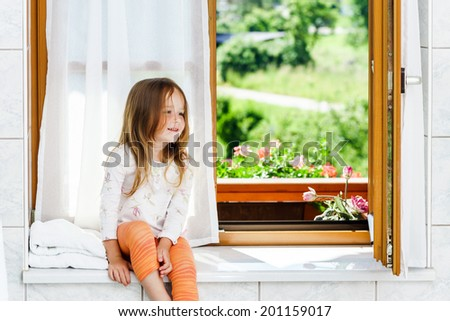Cute little girl sitting on a bathroom window in the house - stock photo