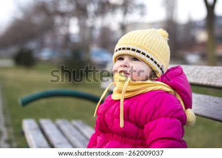 cute little girl sitting on a park bench in winter - stock photo