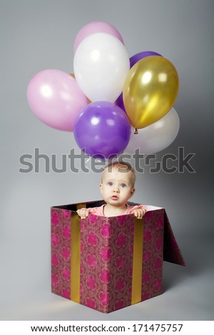 cute little girl sitting on box with balloons - stock photo