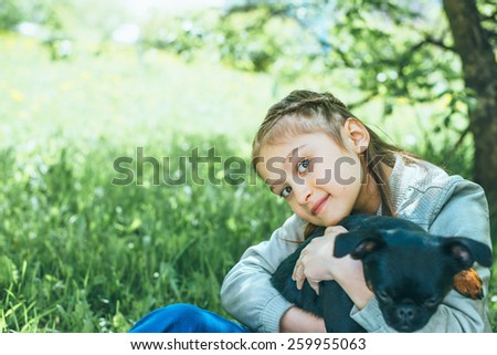 Cute little girl sitting on green grass with her funny dog and  looking at camera - stock photo