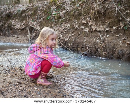 Cute little girl sitting on the Bank of the river in the forest. - stock photo