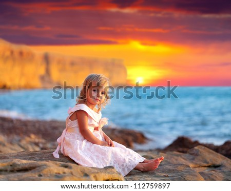 Cute little girl sitting on the beach at sunset - stock photo