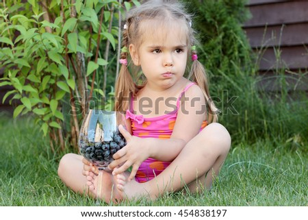 Cute little girl sitting on the grass and eating blueberries from the glass, summertime outdoor, healthy food concept - stock photo