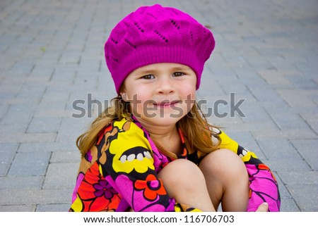Cute little girl sitting outside wearing colorful clothes - stock photo