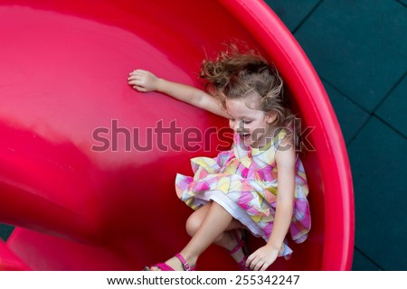 Cute little girl sliding on playground - stock photo