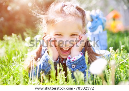 cute little girl smiling in a park close-up - stock photo