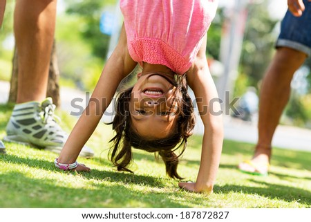 Cute little girl standing on her hands in the backyard - stock photo