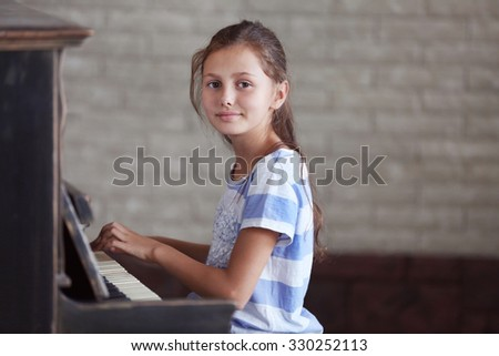Cute little girl studding to play piano - stock photo