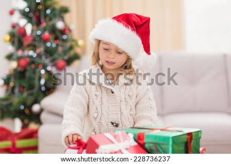 Cute little girl surrounded by christmas gifts at home in the living room - stock photo