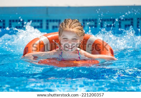 cute little girl swims with a lifeline in the pool in  summer - stock photo