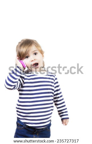 Cute little girl talking with a phone isolated on white. Adorable baby playing to use a mobile - stock photo