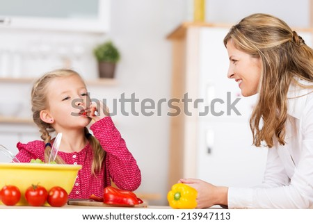 Cute little girl tasting the vegetables as she prepares a meal with her mother in the kitchen chewing on a ripe red cherry tomato with a look of bliss - stock photo