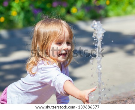 Cute little girl trying to catch the water from the fountain - stock photo
