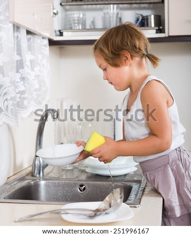 Cute little girl washing dishes in the kitchen - stock photo