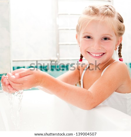 Cute little girl washing in bath - stock photo