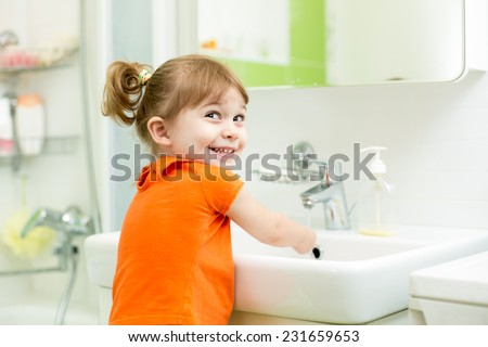 Cute little girl washing in bath room - stock photo