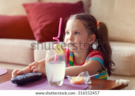 cute little girl watching tv and having lemonade and candy at home.  - stock photo