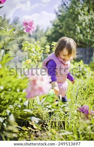 Cute little girl watering flowers in the summer garden - stock photo