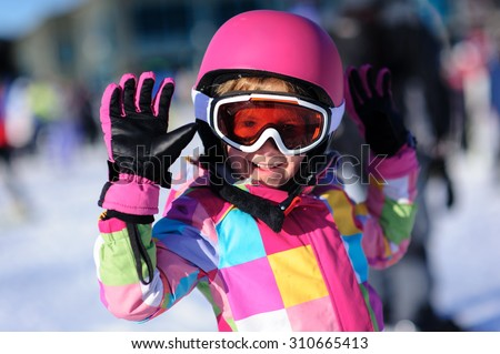 Cute little girl wearing a bright colorful winter jacket and a pink ski helmet and goggles waiving at the camera - stock photo