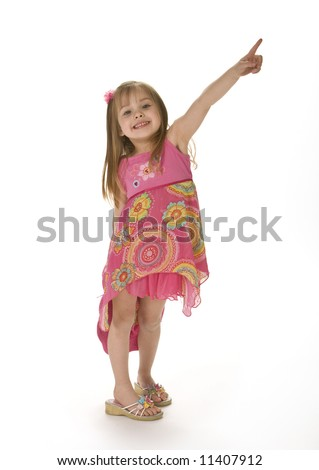 Cute little girl wearing a pink sumer dress smiling and pointing up, isolated on white background. - stock photo